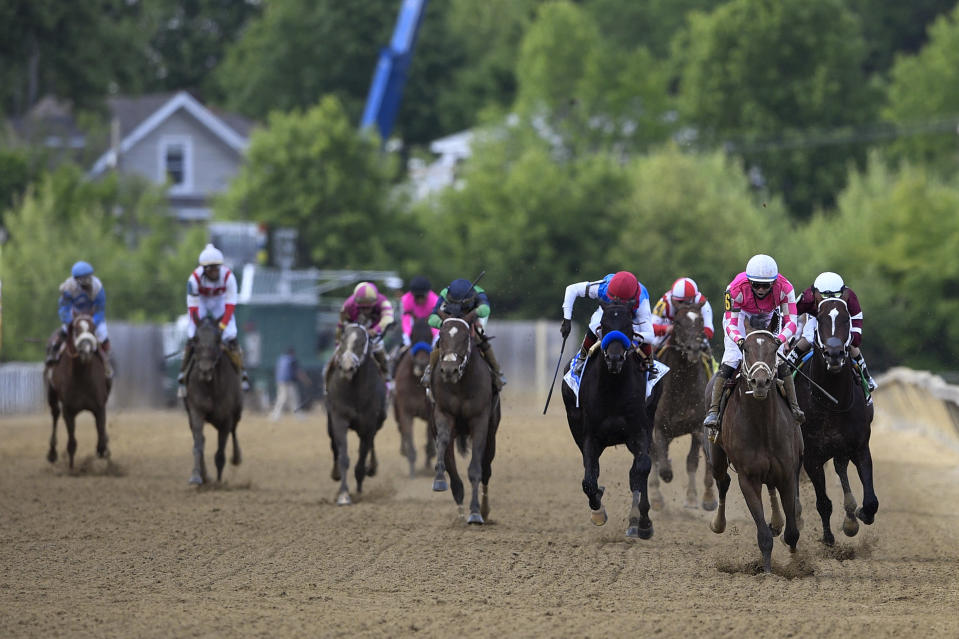 Flavien Prat atop Rombauer, second from right, leads the pack before winning the Preakness Stakes horse race at Pimlico Race Course, Saturday, May 15, 2021, in Baltimore. (AP Photo/Nick Wass)