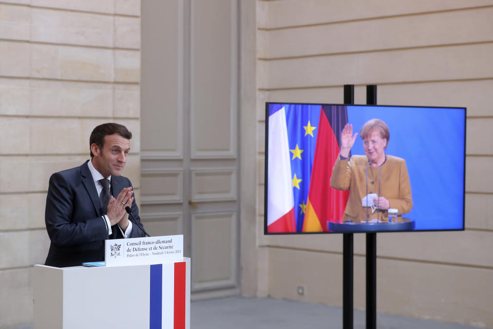 German Chancellor Angela Merkel waves goodbye to French President Emmanuel Macron after a German-French Security Council video conference Friday, Feb. 5, 2021 at the Elysee Palace in Paris. (AP Photo/Thibault Camus, Pool)