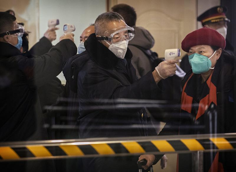 A health worker checks a Chinese passenger arriving on a bullet train from Wuhan to Beijing for symptoms of coronavirus. Train service from Wuhan has since been shut down to contain the spread of the virus.