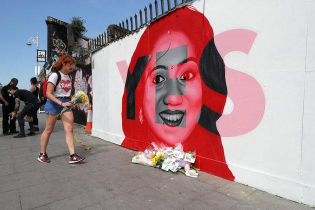 A woman lays flowers next to a mural of Savita Halappanavar in Dublin, as Ireland went to the polls.