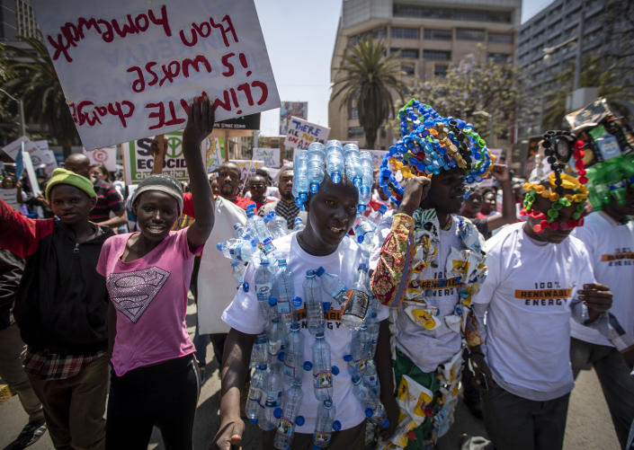 FILE - In this Friday, Sept. 20, 2019 file photo, around a thousand protesters, some wearing outfits made from plastic bottles and bottle-tops to raise the issue of plastic pollution, march to demand action on climate change, in the streets of downtown Nairobi, Kenya. The oil industry in 2020 has asked the United States to pressure Kenya to change its world-leading stance against the plastic waste that litters Africa, according to environmentalists who fear the continent will be used as a dumping ground. (AP Photo/Ben Curtis, File)