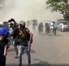 Protesters run away from tear gas in Mandalay