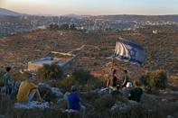 Israeli settler youths lift an Israeli flag in the newly-established wildcat outpost of Eviatar near the northern Palestinian city of Nablus in the occupied West Bank