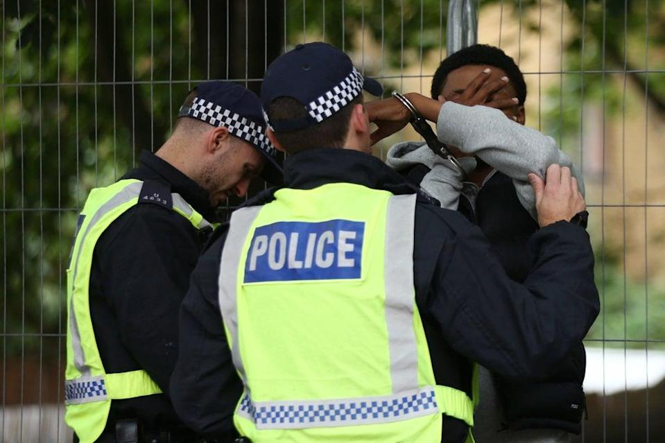 Police officers handcuff a man at the Notting Hill Carnival in west London (PA)
