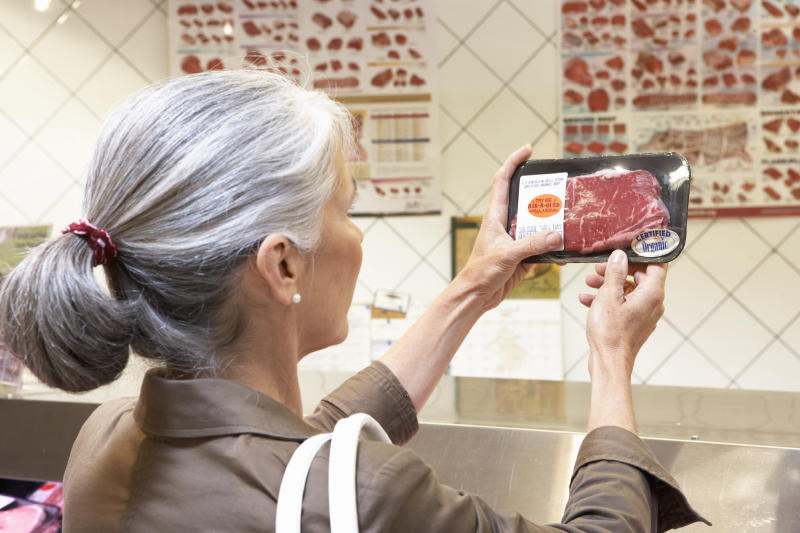 A woman holds up a packaged piece of meat and reads the label. If you're ever in doubt about a product CSIRO recommends checking the label to see what its use by date or best before date is along with how to store it.