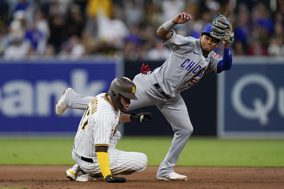 Chicago Cubs shortstop Sergio Alcantara, right, jumps out of the way as San Diego Padres' Victor Caratini arrives safely with a double during the second inning of a baseball game Monday, June 7, 2021, in San Diego. (AP Photo/Gregory Bull)