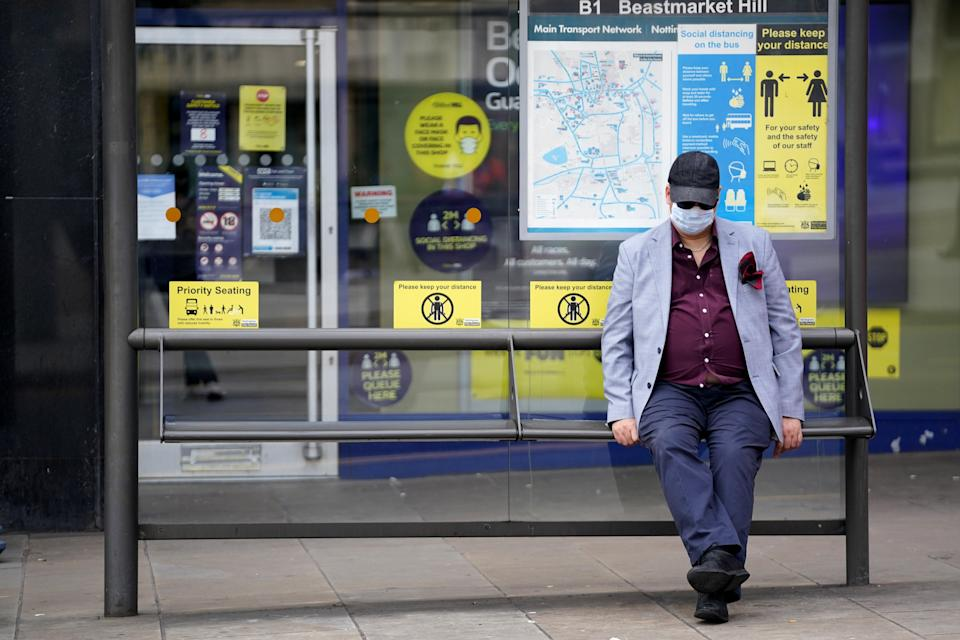 A member of the public wearing a mask sits at a bus stop (Zac Goodwin/PA) (PA Wire)