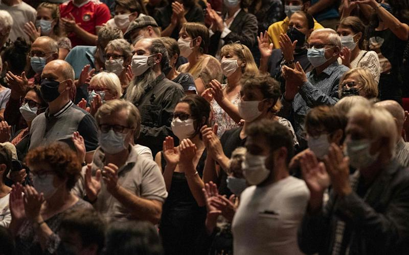 "People wearing protective mask applause at the end of a show called ""Lettre a ma ville"" (letter to my city) at the La Filature concert hall in Mulhouse, eastern France, on September 23, 2020.  - Sebastien Bozon/AFP"