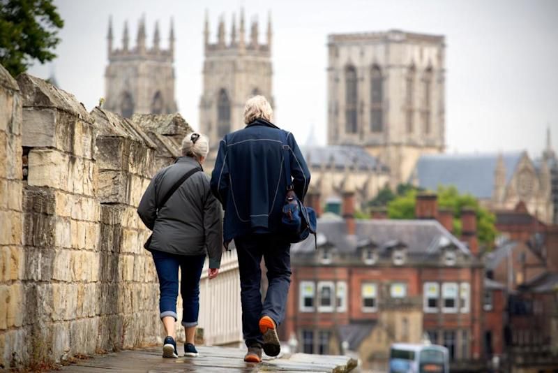 People walk along the Roman city walls towards York Minster and York town centre in North Yorkshire.