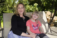 Holly Christensen, left, sits in a swing with her daughter, Lyra, Thursday, May 13, 2021, in Akron, Ohio. Anti-abortion activists say 2021 has been a breakthrough year for legislation in several states seeking to prohibit abortions based on a prenatal diagnosis of Down syndrome. Opponents of the bills, including some parents with children who have Down syndrome like Holly, argue that elected officials should not be meddling with a woman's deeply personal decision on whether to carry a pregnancy to term after a Down syndrome diagnosis. (AP Photo/Tony Dejak)