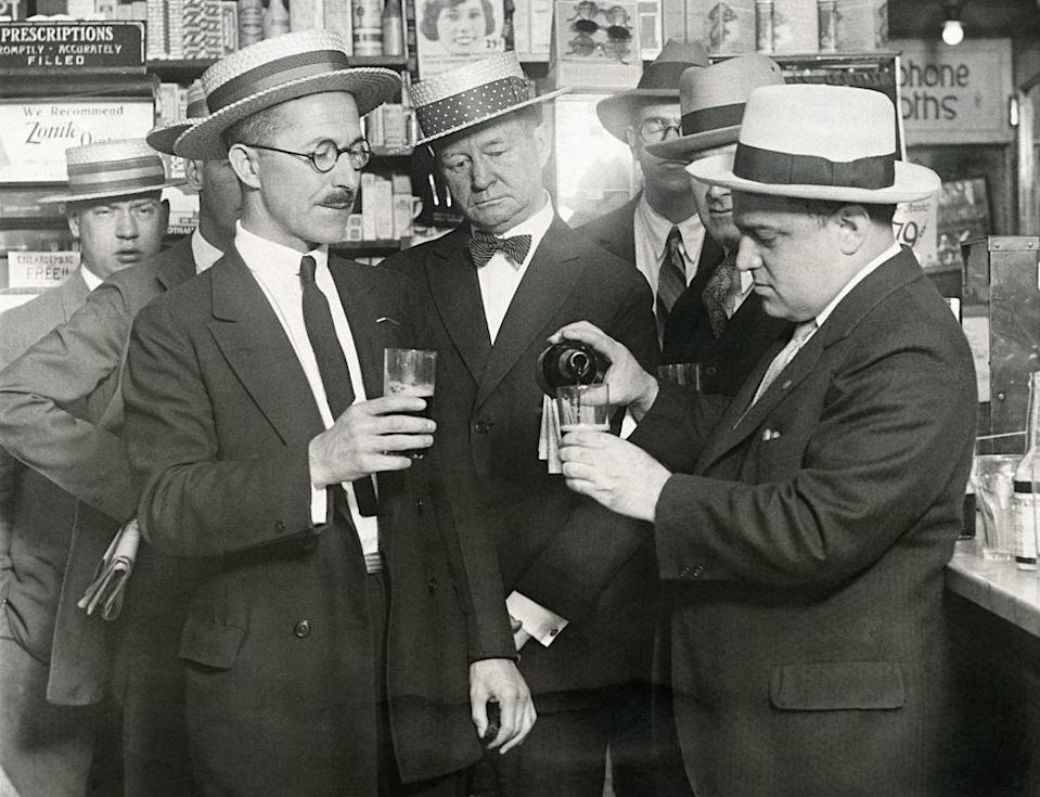 A group of men in a pharmacy pouring glasses of alcohol