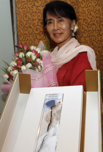 Myanmar opposition leader Aung San Suu Kyi, , receives a posthumous gift from Foreign Minister of Czech Republic Karel Schwarzenberg, during their meeting at a hotel in Naypyitaw, Myanmar, Tuesday, July 17, 2012. Aung San Suu Kyi is no stranger to tributes for her courageous political opposition in Myanmar, but the latest was perhaps the most bittersweet - delivered from beyond the grave from an ardent admirer who was another tenacious fighter for democracy. Czech Foreign Minister Karel Schwarzenberg at a dinner Tuesday night presented her with a dried, yellow rose on behalf of his country's late president, Vaclav Havel, who died in December. The rose, embedded in a glass case, had been laid on Havel's coffin last year by Myanmar democracy activists, and was retrieved by a Czech artist who preserved it. Jiri Sitler, a friend of Havel and former Czech ambassador to Myanmar in Schwarzenberg's delegation, explained to The Associated Press the idea behind the unusual gift. (AP Photo/Khin Maung Win)