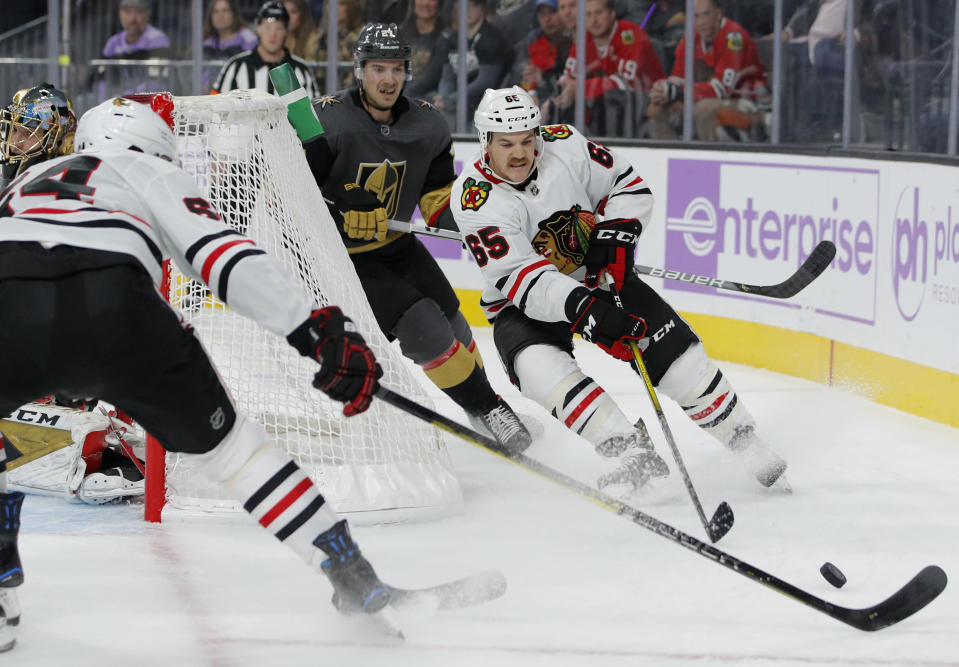 Chicago Blackhawks' Andrew Shaw (65) passes to Chicago Blackhawks' David Kampf (64) against the Vegas Golden Knights during the first period of an NHL hockey game Wednesday, Nov. 13, 2019, in Las Vegas. (AP Photo/John Locher)