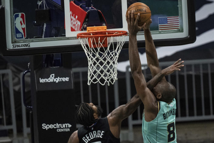 Charlotte Hornets center Bismack Biyombo (8) dunks the ball while guarded by Los Angeles Clippers guard Paul George during the first half of an NBA basketball game in Charlotte, N.C., Thursday, May 13, 2021. (AP Photo/Jacob Kupferman)
