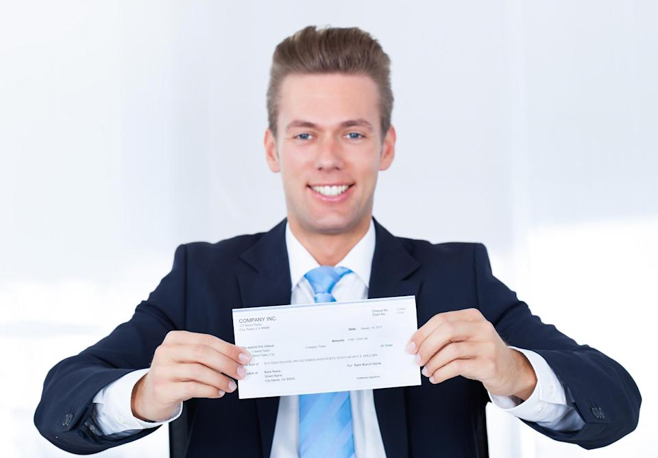 Man in suit holding a check.