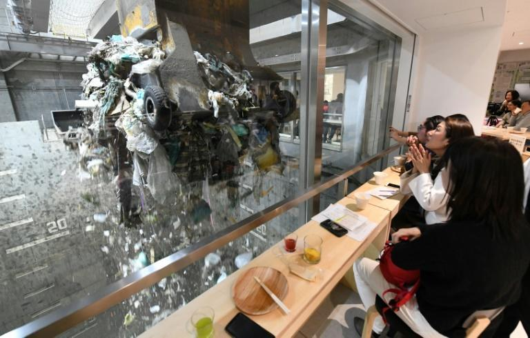 A group of young Japanese enjoy food and drinks while watching an enormous crane pick up trash for incineration at a combustible waste pit in Tokyo