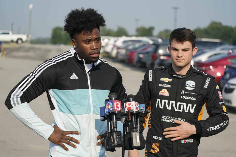 Indianapolis Colts corner back Kenny Moore II, left, talks about arriving in the back seat of a two-seat IndyCar driven by IndyCar driver Pato O'Ward, right, as the players reported to the NFL team's football training camp in Westfield, Ind., Tuesday, July 27, 2021. Practice open on Wednesday. (AP Photo/Michael Conroy)