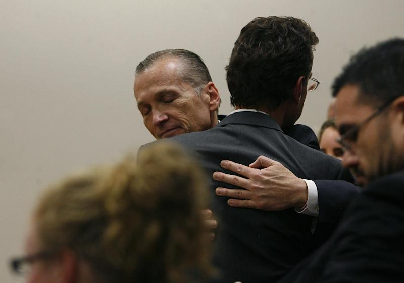 Martin MacNeill hugs attorney Randy Spencer as he thanks his defense team after he was found guilty of murder and obstruction of justice early Saturday morning, Nov. 9, 2013. He faces 15 years to life for first-degree murder when he is sentenced Jan. 7. He also was found guilty of obstruction of justice, which could add 1-15 years. MacNeill was led by deputies back to Utah County jail. (AP Photo/The Salt Lake Tribune, Scott Sommerdorf)