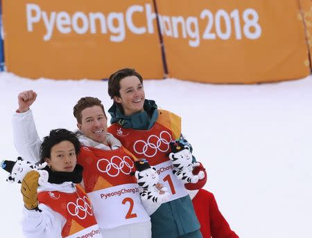 Snowboarding - Pyeongchang 2018 Winter Olympics - Men's Halfpipe Finals - Phoenix Snow Park – Pyeongchang, South Korea - February 14, 2018 - Gold medallist Shaun White of the U.S. is flanked by silver medallist Ayumu Hirano of Japan and bronze medallist Scotty James of Australia during the flower ceremony. REUTERS/Jorge Silva