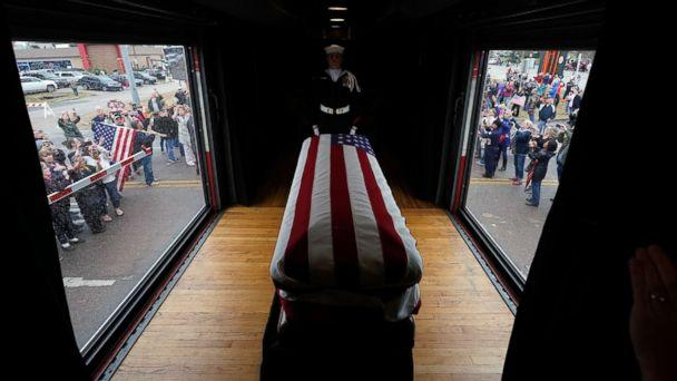 PHOTO: The flag-draped casket of former President George H.W. Bush passes through Magnolia, Texas, Dec. 6, 2018, along the train route from Spring to College Station, Texas. (David J. Phillip/Pool via AP)