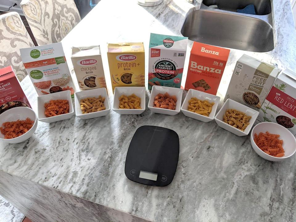 eight boxes of different brands of protein pasta lined up on a kitchen counter next to a kitchen scale