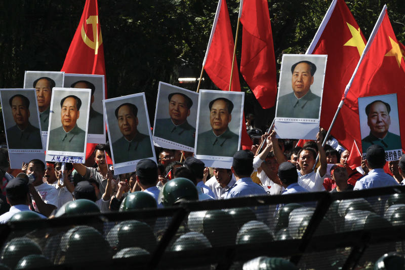 In this Tuesday Sept. 18, 2012 photo, anti-Japan protesters hold portraits of the late Communist leader Mao Zedong and wave Communist party and national flags while marching on the street outside the Japanese Embassy in Beijing, China. The face of dissatisfaction with China's Communist Party is the face of the man synonymous with it: Mao Zedong. Portraits of the revolutionary leader, hoisted by people born after his death 36 years ago, often led packs of demonstrators in protests over Japan's effort last week to bolster its hold on islands claimed by China. (AP Photo/Alexander F. Yuan)
