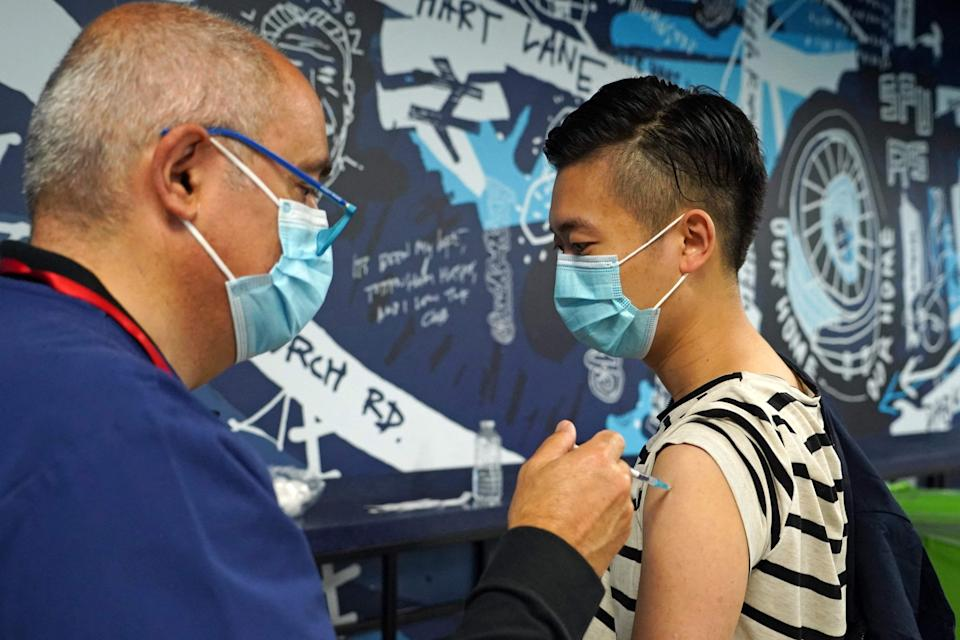 A doctor injects the Pfizer/BioNTech vaccine at a vaccination centre at Tottenham's  stadium (AFP via Getty Images)