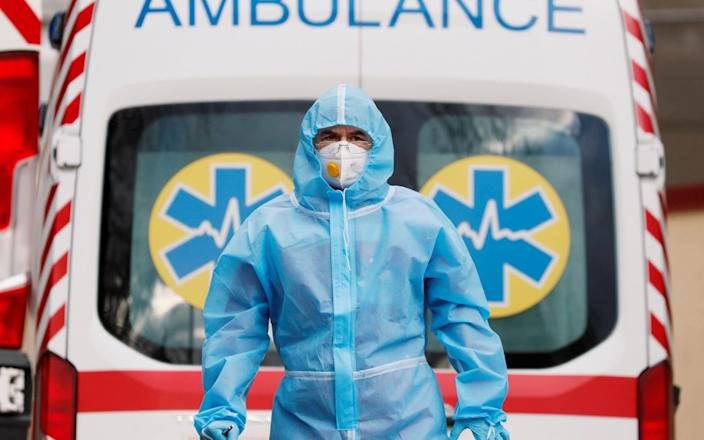 A medical worker wearing protective gear stands next to an ambulance outside a hospital for patients infected with coronavirus in Kyiv - Gleb Garanich/Reuters