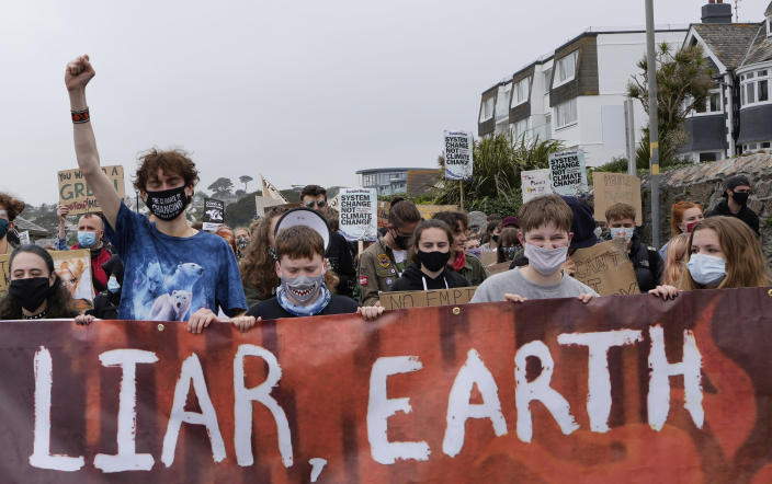 Climate activists hold a banner while marching as they demonstrate as part of Fridays for Future in Falmouth, Cornwall, England, Friday, June 11, 2021. Leaders of the G7 begin their first of three days of meetings on Friday in Carbis Bay, in which they will discuss COVID-19, climate, foreign policy and the economy. (AP Photo/Kirsty Wigglesworth)