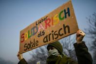 Anti-AfD protesters gathered at the site Friday afternoon -- this woman's banner reads 'rather in solidarity than solid Aryan'