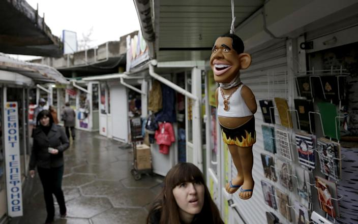 A woman looks at a US President Barack Obama doll at a street market in Simferopol, Crimea, on December 12, 2014 (AFP Photo/Max Vetrov)