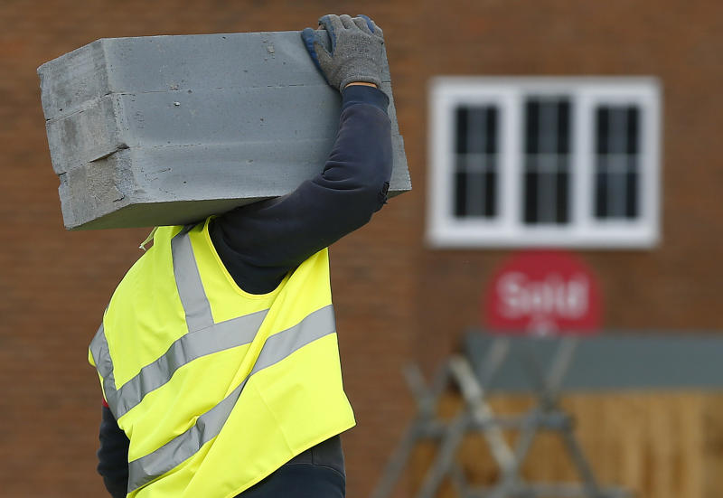 A builder carries blocks on a Barratt Homes building site in Nuneaton, central England March 20, 2014. REUTERS/Darren Staples (BRITAIN)