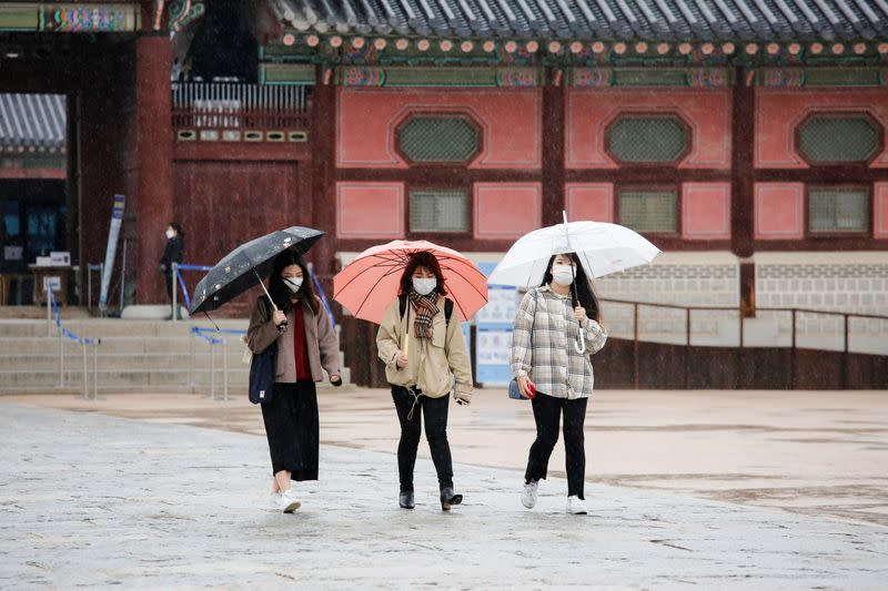 Tourists wearing masks walk with umbrellas as it rains amid the coronavirus disease (COVID-19) pandemic at Gyeongbok Palace in central Seoul