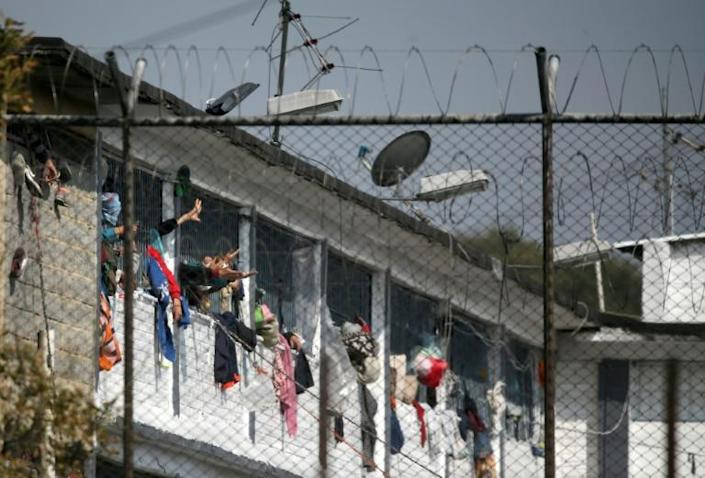 Inmates extend their hands at the Modelo prison in Bogota after a riot on March 22 left 23 prisoners dead and 90 wounded (AFP Photo/DANIEL MUNOZ)