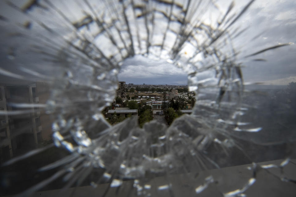 The city of Mekele is seen through a bullet hole in a stairway window of the Ayder Referral Hospital, in the Tigray region of northern Ethiopia, on Thursday, May 6, 2021. While the government now holds many urban centers, fierce fighting continues in remote rural towns. (AP Photo/Ben Curtis)