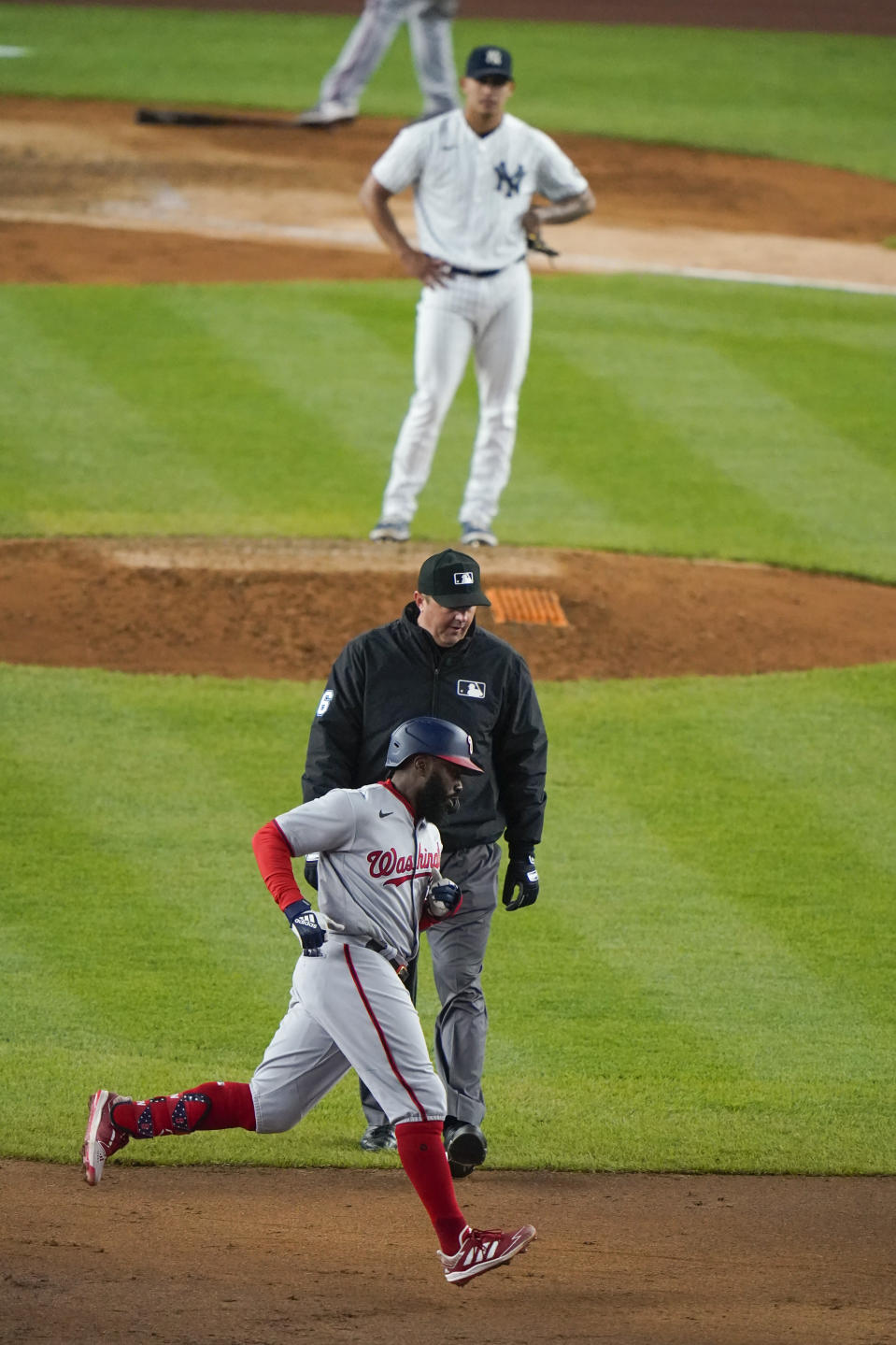 Washington Nationals' Josh Harrison runs the bases after hitting a three-run home run during the eighth inning of a baseball game as New York Yankees starting pitcher Jonathan Loaisiga watches, Friday, May 7, 2021, in New York. (AP Photo/Frank Franklin II)