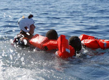 A rescue swimmer holds onto migrants frantically trying to stay afloat after falling off their rubber dinghy during a rescue operation by the Malta-based NGO Migrant Offshore Aid Station (MOAS) ship in the central Mediterranean in international waters some 15 nautical miles off the coast of Zawiya in Libya, April 14, 2017.  REUTERS/Darrin Zammit Lupi