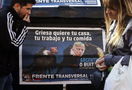 People walk past a poster depicting U.S. Judge Griesa as a vulture in Buenos Aires