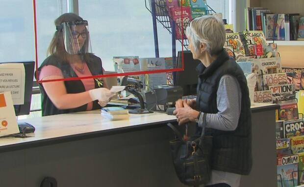 A cashier at a bookstore in Sherbrooke, Que. hands a receipt to a customer under a protective barrier of plexiglass. (CBC/Radio-Canada - image credit)