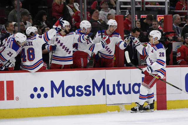 New York Rangers' Chris Kreider (20) celebrates with teammates on the bench after scoring a goal during the second period of an NHL hockey game against the Chicago Blackhawks Wednesday, Feb. 19, 2020, in Chicago. New York won 6-3. (AP Photo/Paul Beaty)