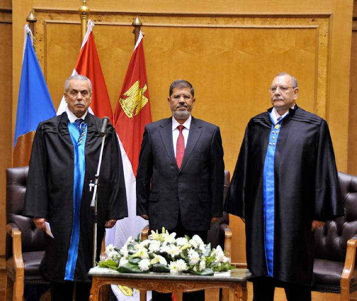 """In this image released by the Egyptian Presidency, Egyptian President Mohammed Morsi, center, stands with judges Farouk Sultan, left, and Maher el-Beheiri, right, as he is sworn in at the Supreme Constitutional Court in Cairo, Egypt, Saturday, June 30, 2012. Islamist Mohammed Morsi promised a """"new Egypt"""" and unwavering support to the powerful military as he took the oath of office Saturday to become the country's first freely elected president, succeeding Hosni Mubarak who was ousted 16 months ago. (AP Photo/Ahmed Fouad, Egyptian Presidency)"""