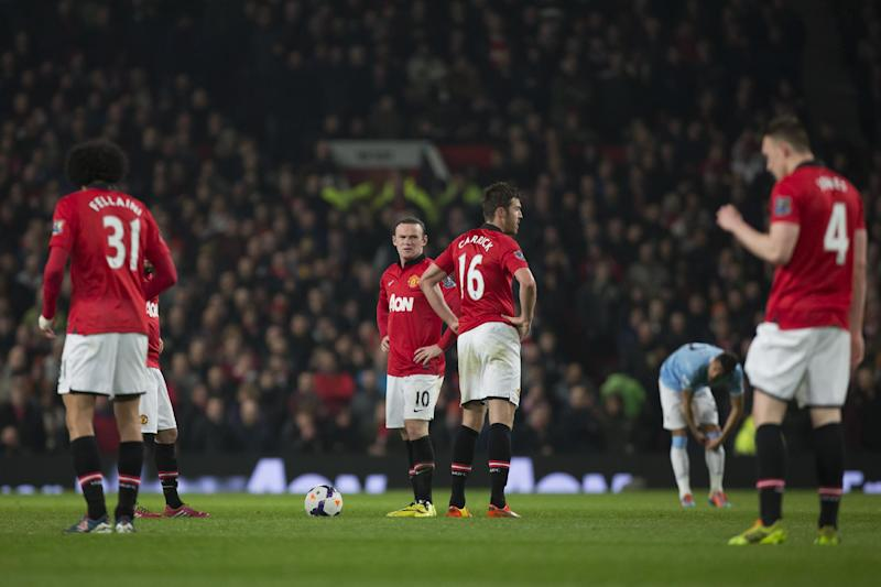 Manchester United's Wayne Rooney, center, and Michael Carrick, center right, wait with teammates for play to begin after a second goal by Manchester City's Edin Dzeko, out of frame, during their English Premier League soccer match at Old Trafford Stadium, Manchester, England, Tuesday March 25, 2014. (AP Photo/Jon Super)