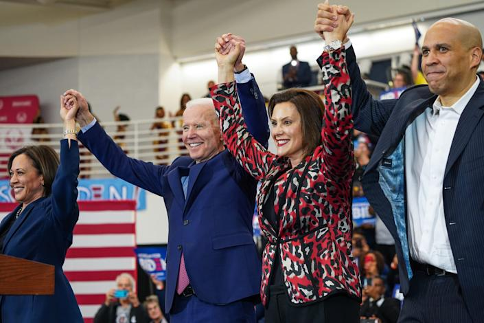 (Left to right) U.S. Sen. Kamala Harris of California, Democratic presidential candidate and former Vice President Joe Biden, Michigan Governor Gretchen Whitmer and U.S. Sen. Cory Booker raise arms after Biden takes the stage to speak to a crowd during a Get Out the Vote event at Renaissance High School in Detroit on Monday, March 9, 2020.