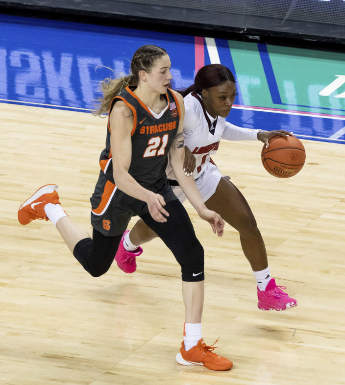 Louisville's Dana Evans (1) dribbles past Syracuse's Emily Engstler (21) during the first half of an NCAA college basketball game in the semifinals of Atlantic Coast Conference tournament in Greensboro, N.C., Saturday, March 6, 2021. (AP Photo/Ben McKeown)