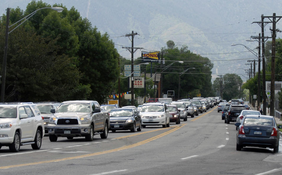Traffic moves as smoke billows from a wildfire west of Colorado Springs, Colo. on Saturday, June 23, 2012. The fire has grown to an estimated 600 acres and The Gazette reports authorities are evacuating the exclusive Cedar Heights neighborhood as well as the Garden of the Gods nature center. (AP Photo/Bryan Oller)