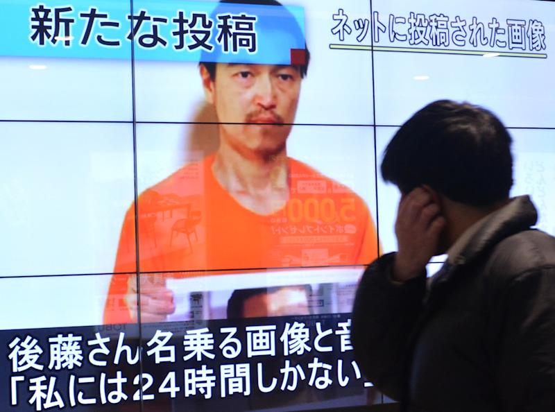 A pedestrian looks at a large screen in Tokyo on January 28, 2015 showing television news reports about Japanese hostage Kenji Goto who has been kidnapped by the Islamic State group (AFP Photo/Kazuhiro Nogi)