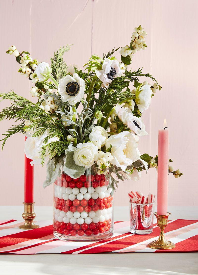 """<p>Talk about a great hostess gift! Place a small pillar vessel inside a larger vase, and fill the gaps between the two with red and white marbles. Contrast the colorful stack with anemones, garden roses, and evergreen sprigs. </p><p><a class=""""link rapid-noclick-resp"""" href=""""https://www.amazon.com/s/ref=nb_sb_noss_2?url=search-alias%3Daps&field-keywords=marbles&tag=syn-yahoo-20&ascsubtag=%5Bartid%7C10050.g.645%5Bsrc%7Cyahoo-us"""" rel=""""nofollow noopener"""" target=""""_blank"""" data-ylk=""""slk:SHOP MARBLES"""">SHOP MARBLES</a></p>"""