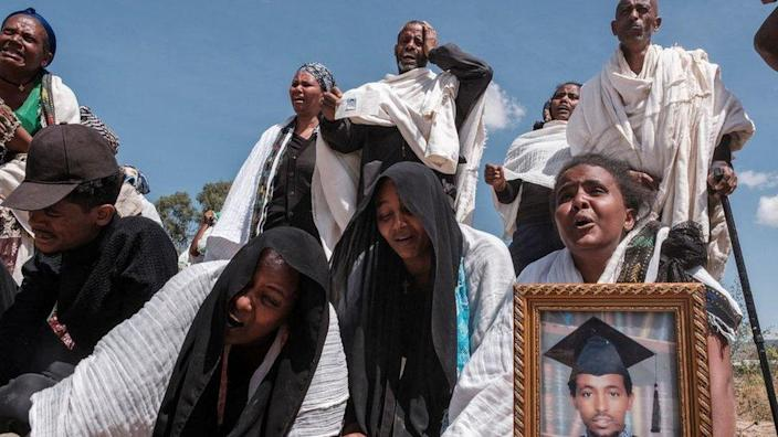 People react as they stand next to a mass grave containing the bodies of 81 victims of Eritrean and Ethiopian forces, killed during violence of the previous months, in the city of Wukro, north of Mekele, on February 28, 2021.