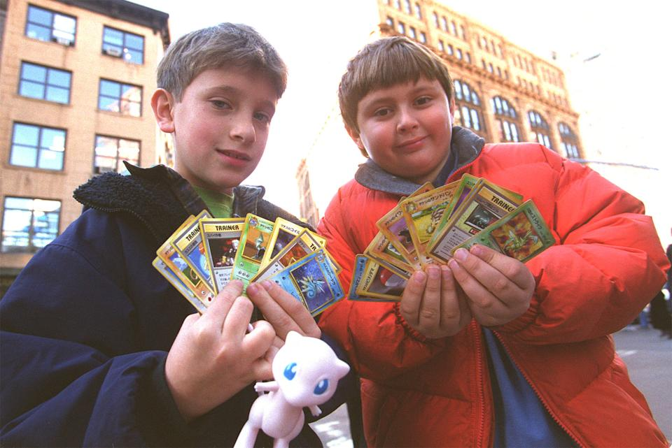 Two children display their Pokemon cards in New York city November 12, 1999. In anticipation of the overwhelming demand for the new limited edition Pokemon trading cards being given away in conjunction with the November 10 release of Kids'' WB! Presents
