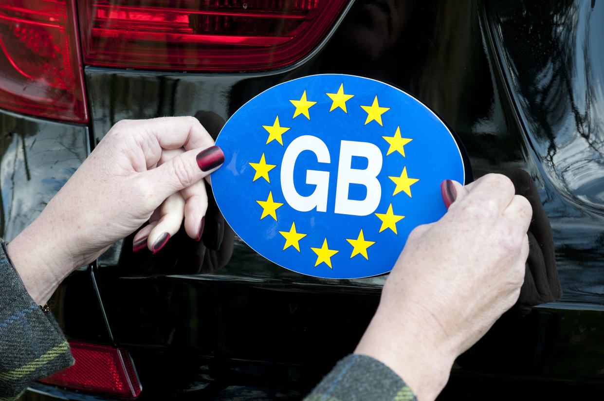 Woman's hands attaching a GB sticker to the rear of a car. (Photo by: Education Images/Universal Images Group via Getty Images)